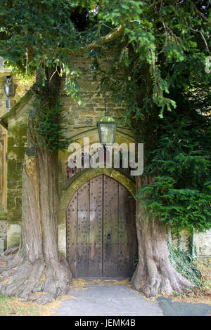 Yew trees flanking door in the north porch of St Edwards parish church in Stow on the Wold - Stock Photo