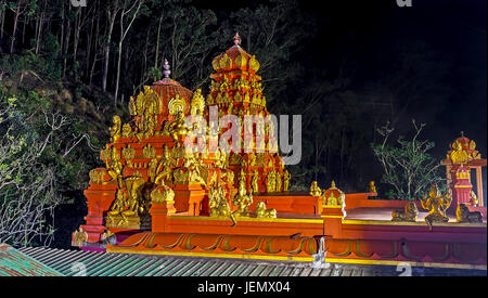 The brightly illuminated vimana and shikhara towers with golden sculptures are seen in dark night, Seetha Amman - Stock Photo
