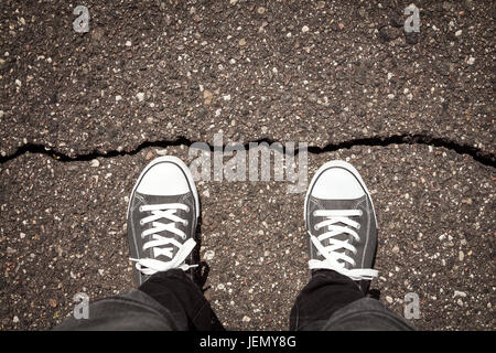 Man standing on cracked damaged city asphalt floor - Stock Photo