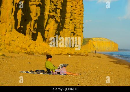 West Bay, Dorset, UK. 26th June, 2017. UK Weather. A woman sits reading a newspaper with a view of part of the cliff - Stock Photo