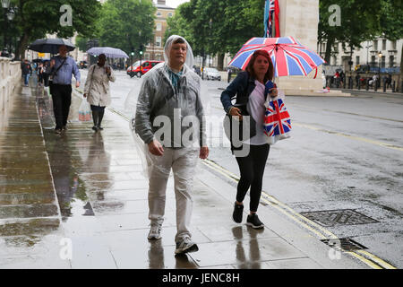 Westminster. London, UK. 27th June, 2017. People take shelter from the rain under umbrellas in Westminster after - Stock Photo