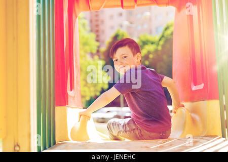 happy little boy on slide at children playground - Stock Photo