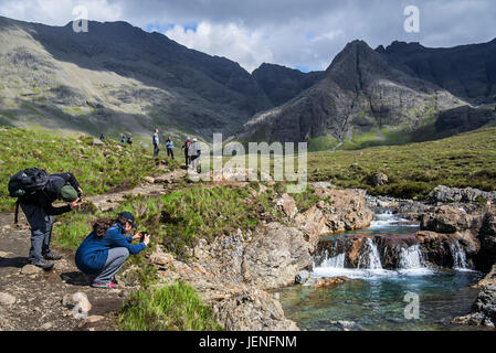 Walkers taking pictures of the Fairy Pools, succession of waterfalls in Glen Brittle on the Isle of Skye, Scottish - Stock Photo