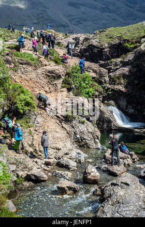 Large group of tourists visiting the Fairy Pools, succession of waterfalls in Glen Brittle on the Isle of Skye, - Stock Photo