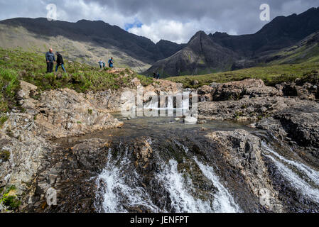 Black Cuillin and tourists visiting the Fairy Pools, succession of waterfalls in Glen Brittle on the Isle of Skye, - Stock Photo