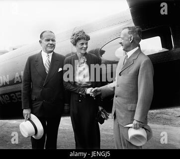 Amelia Earhart, Center, Portrait Shaking Hands with Man in front of Airplane, Harris & Ewing, 1932 - Stock Photo