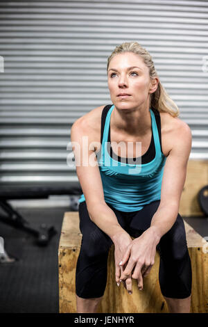 Fit woman sitting on wooden box - Stock Photo