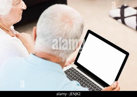 Focused senior couple using laptop - Stock Photo