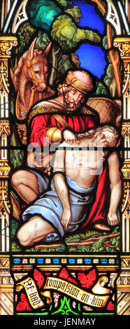 Good Samaritan Parable, tending traveller's injuries, giving water, 'He had compassion on him', stained glass window, - Stock Photo