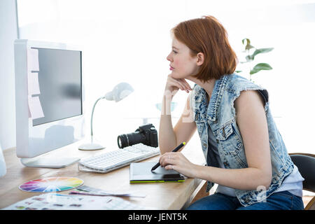 smiling hipster photographer on her tablet - Stock Photo