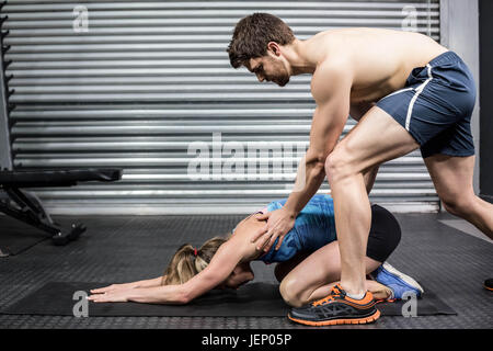 Male trainer assisting woman stretching - Stock Photo