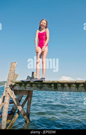 girl wearing flippers on jetty - Stock Photo