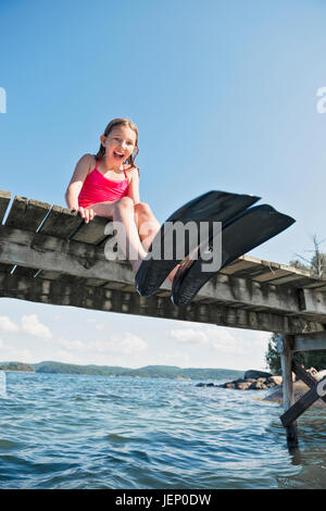 Happy girl wearing flippers on jetty - Stock Photo