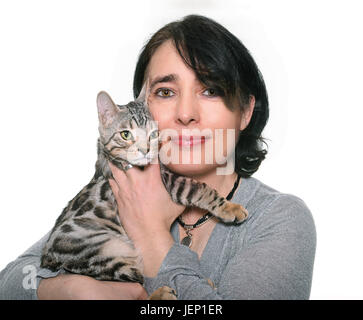 bengal kitten and woman in front of white background - Stock Photo
