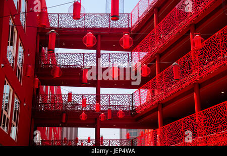 A red building exterior and red lanterns hanging from wires near the chinatown metro station in Los Angeles California - Stock Photo
