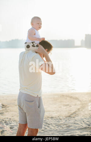 father carrying baby on shoulders at beach - Stock Photo