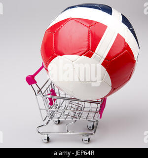 football ball in ping shopping cart on white background - Stock Photo