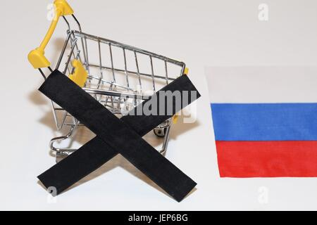 Shopping cart and black in front of a Russian flag simbolize stop of food import to Russia - Stock Photo