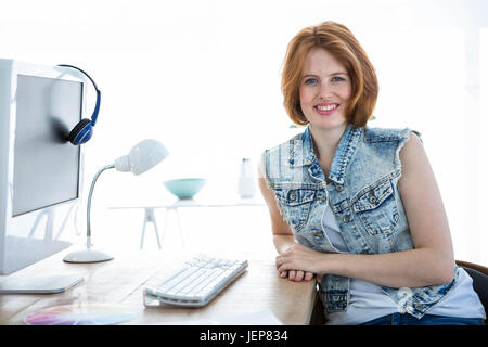 smiling hipster woman sitting at a desk - Stock Photo