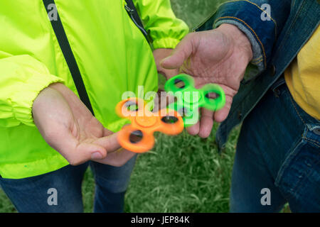 trendy fidget spinner - two persons holding spinning green and orange fidget spinners in hands, close up above view - Stock Photo