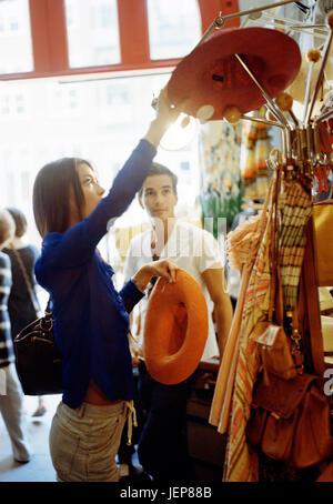 Young woman looking at hats - Stock Photo