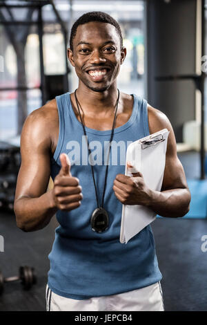 Smiling trainer showing thumbs up - Stock Photo