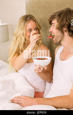 Cute couple having breakfast in bed - Stock Photo