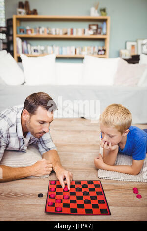 Father and son playing checker game at home - Stock Photo