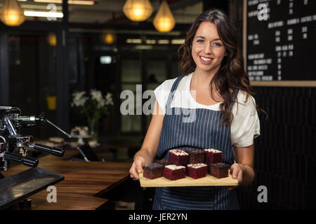 Smiling barista holding plate with cakes - Stock Photo