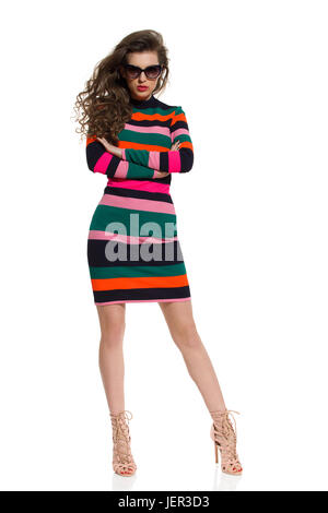 Beautiful young woman in colorful striped mini dress, sunglasses and high heels is posing with arms crossed. Full - Stock Photo