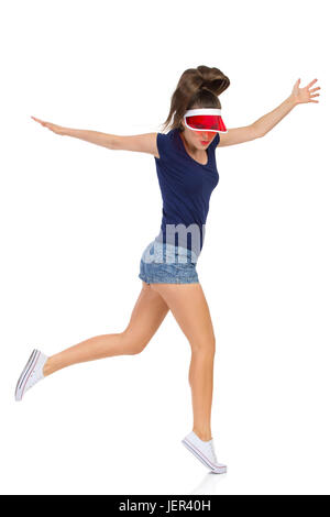Woman in blue shirt, jeans shorts white sneakers and red sun visor cap dancing on one leg with arms outstretched. - Stock Photo