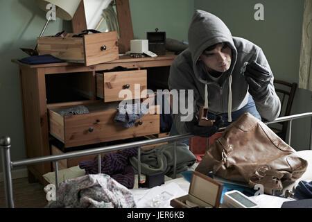 Burglar Stealing Items From Bedroom During House Break In - Stock Photo