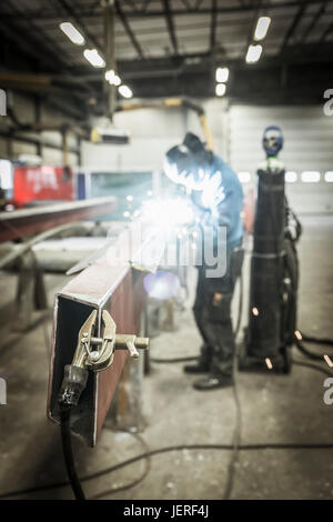 Clamp on metal structure, man welding on background - Stock Photo