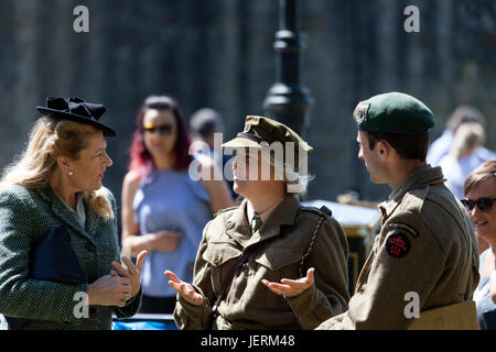 Three People Chatting While Wearing 1940's Style Clothing and Military Uniforms During the 2017 Barnard Castle 1940's Weekend, County Durham, UK.