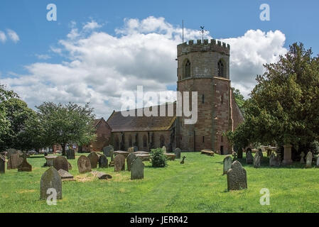 A horizontal image of a typical english country village church standing in a cemetery and taken on a sunny day with - Stock Photo