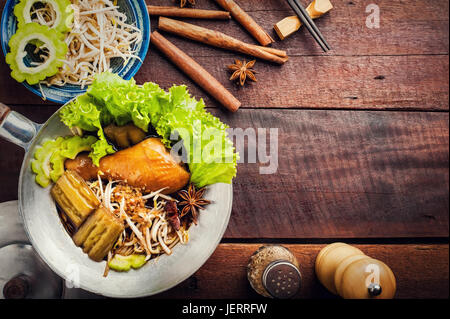 Chicken noodle with spice, herb and chopsticks on wood background - Stock Photo