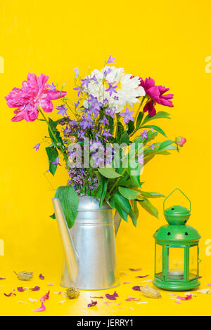 A still life with a beautiful white and purple peonies bouquet and a green lantern against the blurred yellow background - Stock Photo