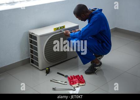 Handyman testing air conditioner - Stock Photo