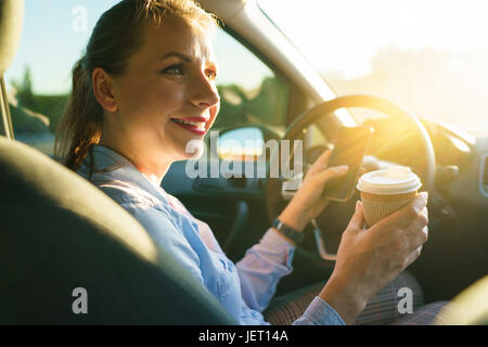 Young businesswoman sending a text message and drinking coffee while driving a car - Stock Photo