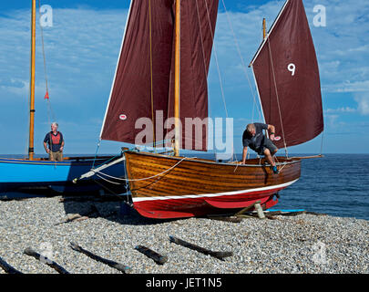 Men rigging boat (lugger) on the beach, Beer, Devon, England UK - Stock Photo