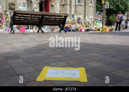 Twelve days after the devastating fire that killed an unspecified number of people in Grenfell Tower, yellow tape - Stock Photo