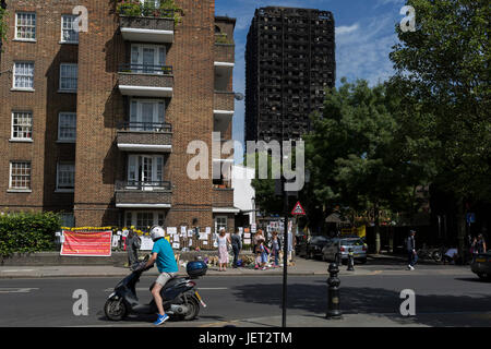 Twelve days after the devastating fire that killed an unspecified number of people in Grenfell Tower, bystanders - Stock Photo