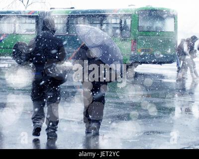 people walking on city street under snowing - Stock Photo
