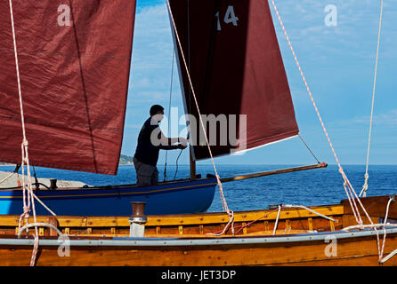 Man rigging boat (lugger) on the beach, Beer, Devon, England UK - Stock Photo