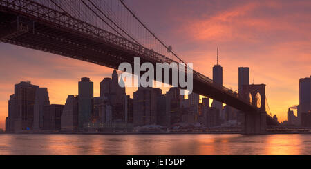 Brooklyn Bridge with the New York City skyline in the background, photographed at sunset. - Stock Photo