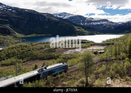 Flam Railway train journey through lake and mountain landscape in summer. Vatnahelsen, Aurland, Norway, Scandinavia, - Stock Photo