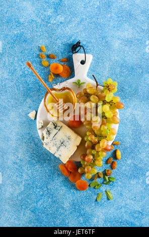 Ripe grapes, gorgonzola cheese, honey and dried fruits on a white marble board. Summer refined light snack on a - Stock Photo