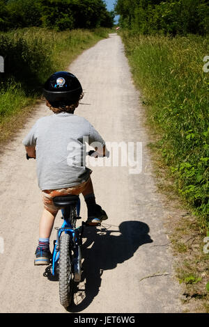 A boy cycles along a dirt track along a disused railway line in the summer sun - Stock Photo