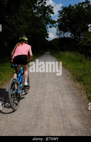 A girl cycles along a dirt track along a disused railway line in the summer sun - Stock Photo