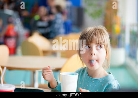 Cute blonde girl sticking or poking tongue out with blue crushed ice drink in brightly lit natural light cafe or - Stock Photo